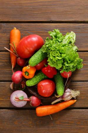 onion: varias verduras para una ensalada de pepinos, tomates, lechuga, r�banos, zanahorias en el fondo de madera