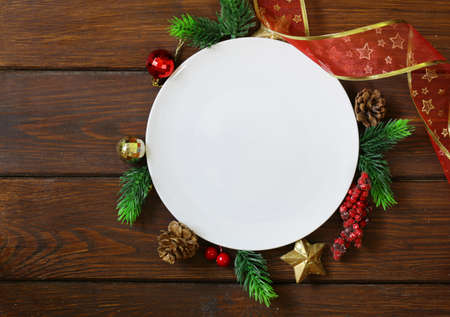 food       plate: Christmas wooden background with fir branches, decoration and white plate