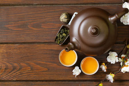tea set teapot, cups and different green tea a wooden background, top view