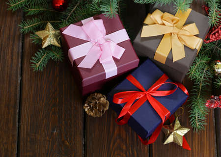 cajas navideñas: gift boxes with festive ribbons and Christmas decorations on a wooden background Foto de archivo