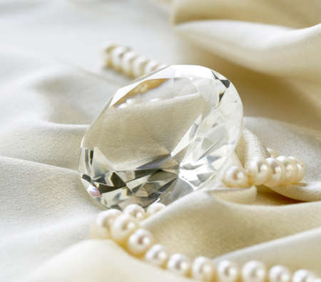 perlas: gran diamante de cristal y collar de perlas en un fondo de seda suave