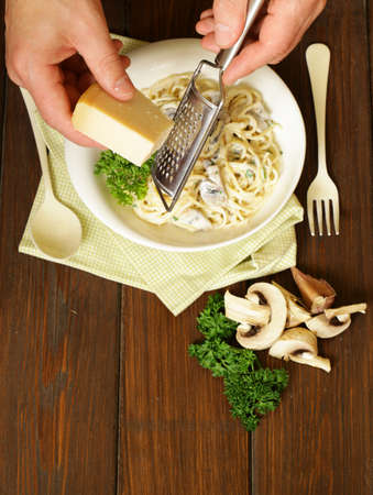 cheese grater: Chef grate parmesan cheese on pasta  carbonara, top view