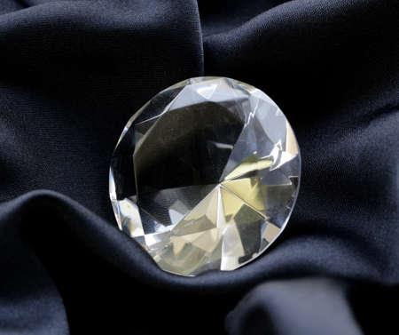 diamante negro: gran diamante de cristal en el fondo suave de seda negro Foto de archivo