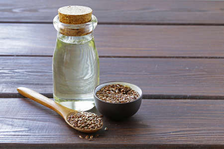 flax seed oil: flax seed oil in glass bottle on a wooden table