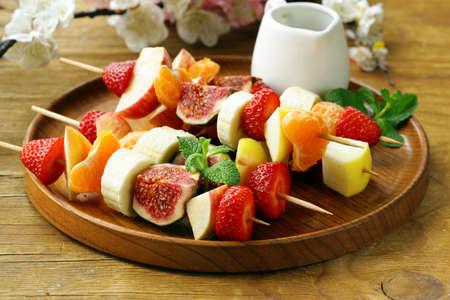 brochetas de frutas: fruta en brochetas de madera - pinchos postre Foto de archivo