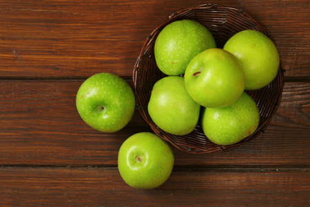 green apples: Fresh organic green apples in a basket on a wooden background Stock Photo
