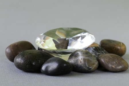diamond stones: large glass diamond among ordinary gray stones