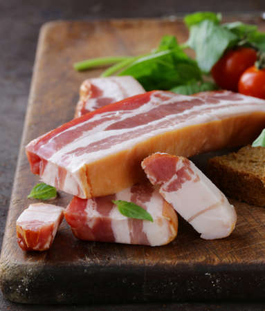 smoked bacon: smoked bacon with basil and tomatoes on a cutting board Stock Photo