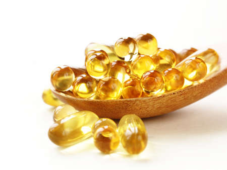 food supplement: food supplement of fish oil capsules in a wooden spoon - healthy food