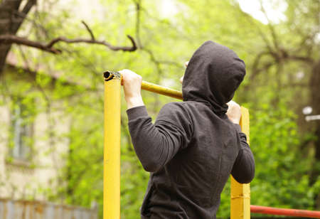 and the horizontal man: man pulled on a horizontal bar, exercise outdoors