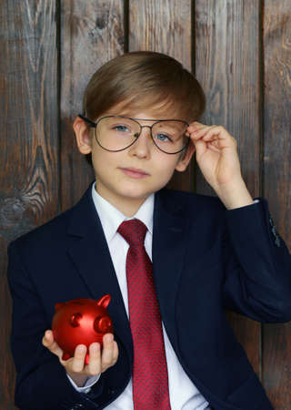 son deposit: Boy in a suit with a red piggy bank - business concept