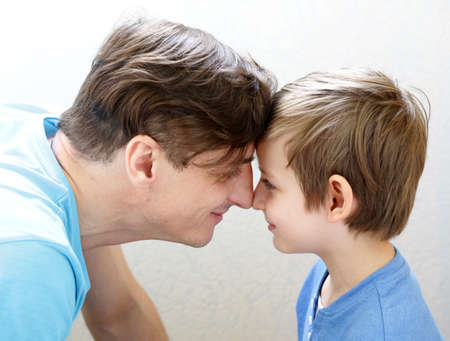 each: father and son look at each other, family and happiness