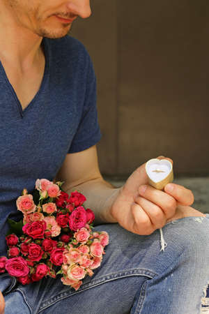rose ring: man with  bouquet of roses and diamond ring, ready to make a proposal