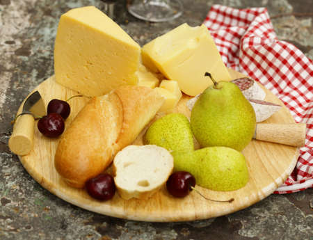 wood product: cheeseboard with pears and wine on a table in the garden