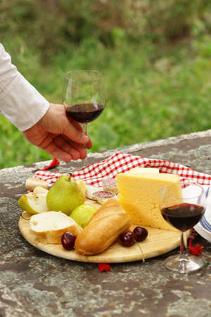 cheeseboard: cheeseboard with pears and wine on a table in the garden