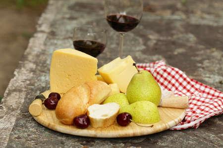 tabla de quesos: tabla de quesos con las peras y el vino en una mesa en el jardín