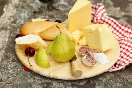 tabla de quesos: cheeseboard with pears and wine on a table in the garden