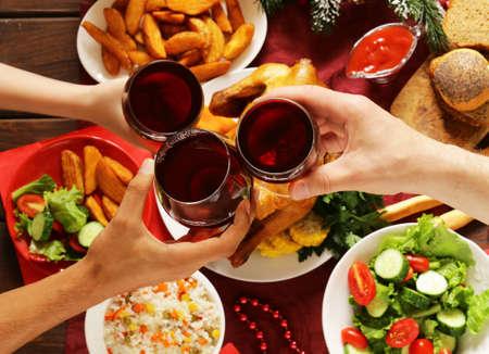 Family toasting red wine glasses and having Christmas dinner