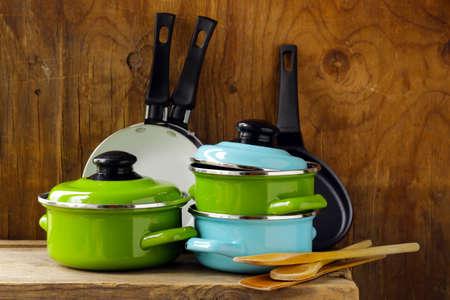 set of metal pots cookware on a wooden, domestic kitchen Standard-Bild