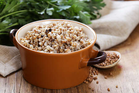 seed pots: Natural organic buckwheat cereal. Boiled buckwheat porridge in a pot. Stock Photo