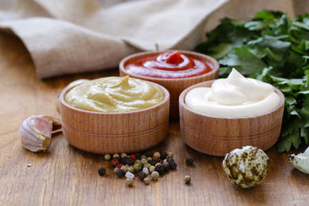 sweet mustard: Ketchup, mayonnaise and mustard - three kinds of sauce in a wooden bowl