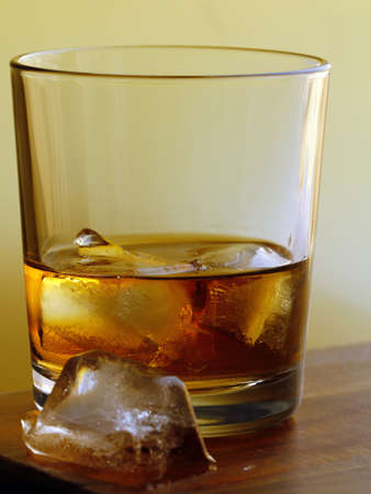 glass of whiskey with ice on a gold background
