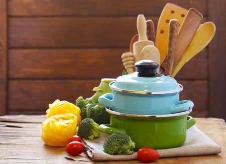 Keukengerei - potten en bestek op een houten tafel Stockfoto