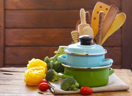 Kitchen tools - pots and cutlery on a wooden table Stock Photo