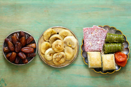 Eastern sweets (baklava, rahat loachum) and dried fruits on a silver plate