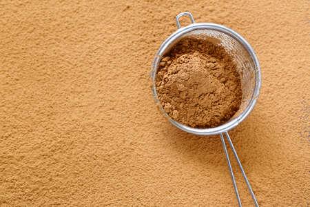 Cacaopoeder in een zeef op een tafel Stockfoto