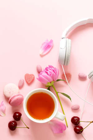 A cup of tea for a woman, macaroon, flowers and sweets on a pink background