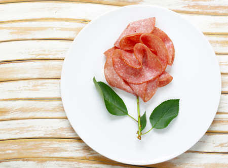 Sliced sausage salami with thyme and pepper Stock Photo