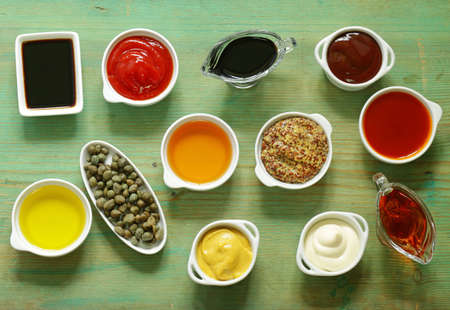 Different types of sauces and oils in bowls, top view Stock Photo