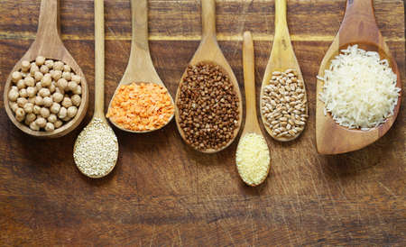 seeds of various: Different types of cereals in wooden spoons - buckwheat, chickpeas, rice, quinoa, lentils Stock Photo