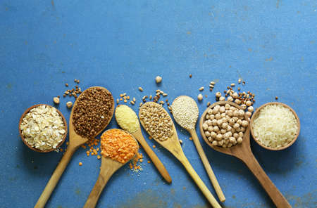 Different types of cereals in wooden spoons - buckwheat, chickpeas, rice, quinoa, lentils Stock Photo