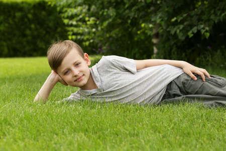 Leuke jonge jongen rusten op het groene gras - zomertijd, picknick Stockfoto