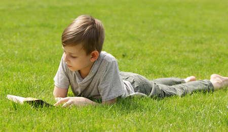 Carino ragazzo biondo che legge un libro in un parco all & # 39 ; aperto Archivio Fotografico - 81082872