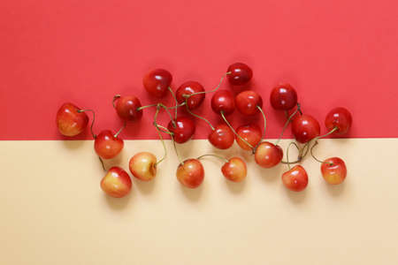 Ripe red and yellow cherry on a colored background