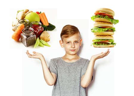 chico rubio elige entre comida sana y comida rápida Foto de archivo
