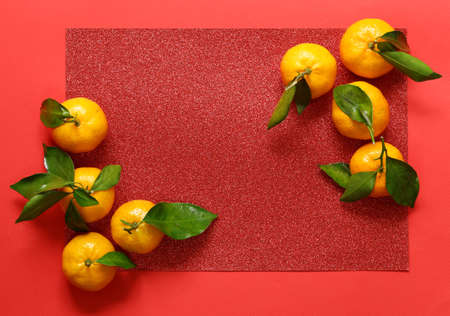 orange organic mandarins on a red background - oriental new year Stock Photo