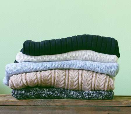 warm knitted sweaters on a wooden shelf Stok Fotoğraf