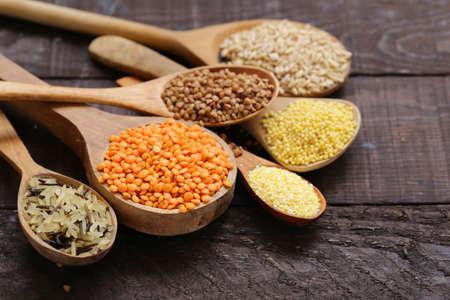 various cereals in wooden spoons - healthy food