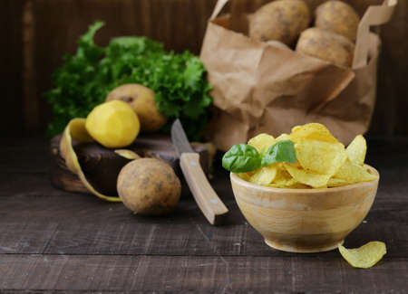 natural potato chips on a wooden table Banque d'images - 118566001
