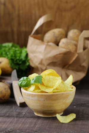 natural potato chips on a wooden table Banque d'images - 118566002