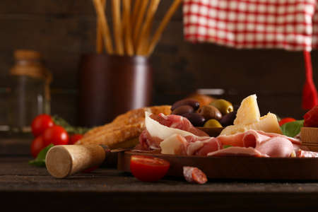 Italian food, prosciutto, olives, cheese and tomatoes
