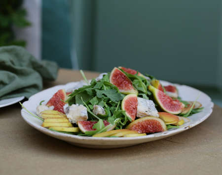 Fresh gourmet salad with figs, cheese and arugula