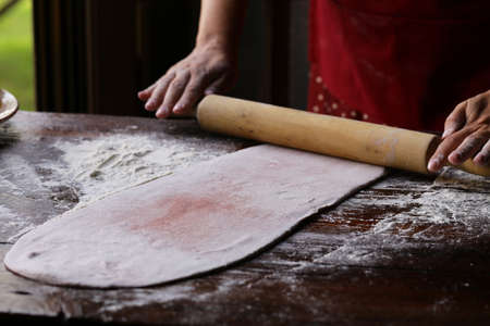female hands with dough make homemade pasta