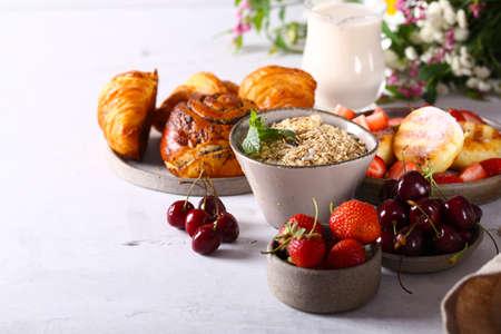Breakfast assortment of cheesecakes rolls muesli and fresh berries