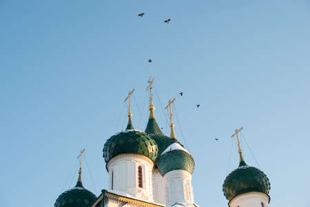 Few domes with crosses over a white-stone temple against a blue sky Banco de Imagens