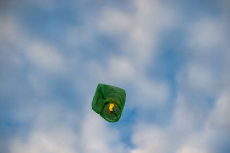 Green paper Chinese lantern flying away to the sky